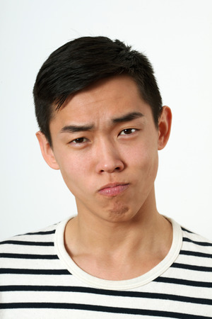 making face: Strict young Asian man making face and looking at camera.