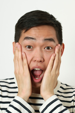 wondered: Astonished young Asian man covering his face with palms.