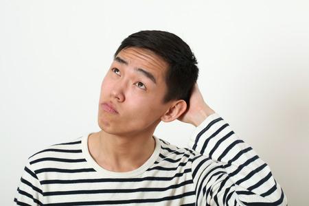 wondered: Thoughtful young Asian man looking upward.