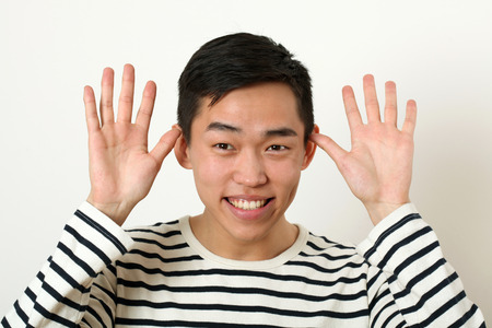 making face: Funny young Asian man making face and looking at camera.
