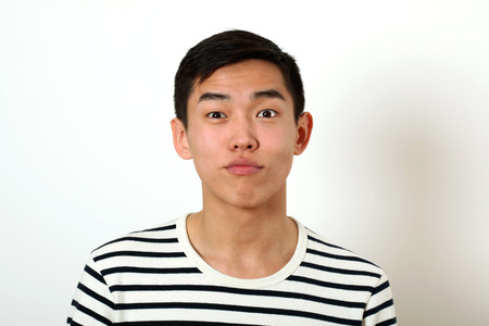 wondered: Funny young Asian man looking at camera. Stock Photo