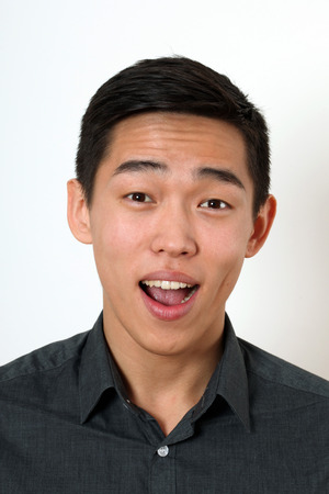 wondered: Laughing young Asian man looking at camera. Stock Photo