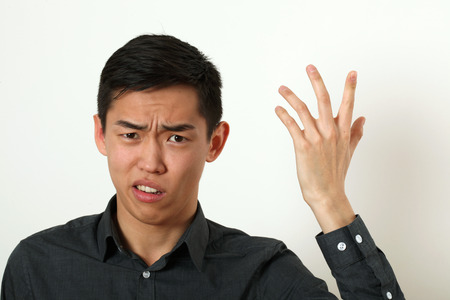 displeasure: Displeased young Asian man gesturing with his hand.