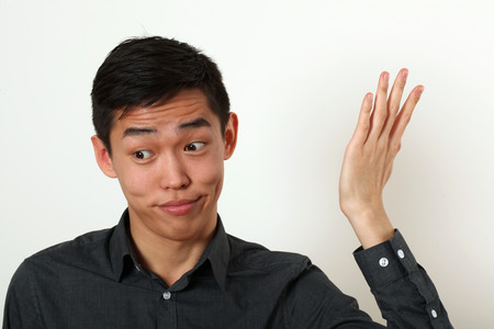 Displeased young Asian man gesturing with his hand.