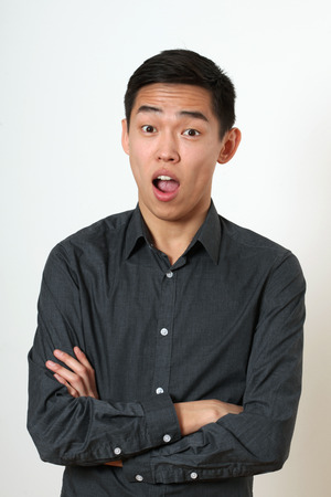 look pleased: Astonished young Asian man with crossed hands looking at camera. Stock Photo