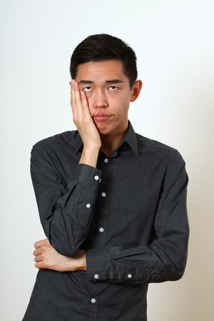 Frustrated young Asian man covering his face with a palm. 스톡 콘텐츠
