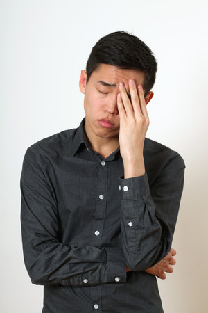 asian man face: Frustrated young Asian man covering his face with a palm. Stock Photo