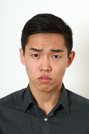 strict: Strict young Asian man looking at camera.