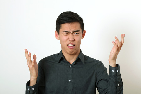 displeased: Displeased young Asian man gesturing with two hands. Stock Photo