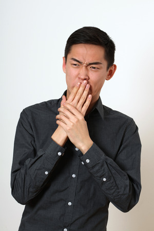 disgusted: Disgusted young Asian man covering his mouth with hands. Stock Photo