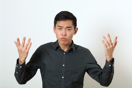 displeasure: Displeased young Asian man gesturing with two hands. Stock Photo