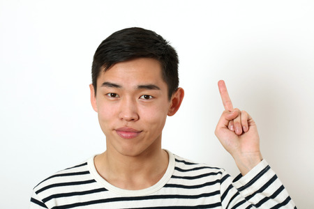 giving the finger: Displeased young Asian man giving the middle finger sign and looking at camera.