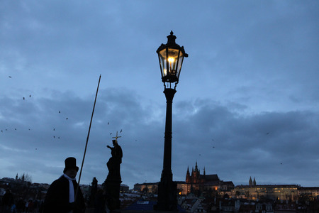 manually: PRAGUE CZECH REPUBLIC  DECEMBER 10 2012: Lamplighter lights a street gas light manually during the Advent at the Charles Bridge in Prague Czech Republic. Street gas lights in the historical centre of Prague are lighted manually during the Advent only as a