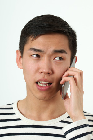 Angry young Asian man using a smartphone. photo