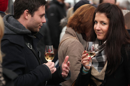 tastes: PRAGUE CZECH REPUBLIC  NOVEMBER 11 2012: Young couple tastes young wine during the celebration of Saint Martin Day in Prague Czech Republic.