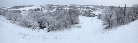 snowcovered: Russian winter. Snow-covered landscape with the village of Kruppsk next to the Izborsk Fortress near Pskov, Russia. Stock Photo