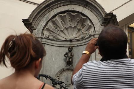 BRUSSELS, BELGIUM - AUGUST 13, 2012: Tourists look at the Manneken Pis in Brussels, Belgium.