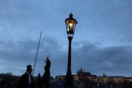 gas lighter: PRAGUE, CZECH REPUBLIC - DECEMBER 10, 2012: Lamplighter lights a street gas light manually during the Advent as the Czech Christmas traditions at the Charles Bridge in Prague, Czech Republic. Editorial
