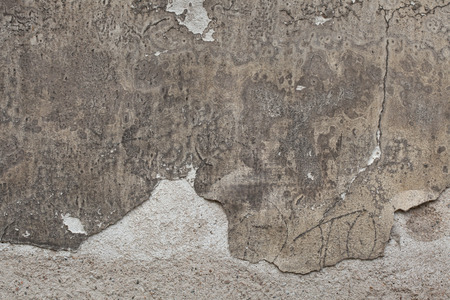 cracked wall: Old grey stucco wall with cracked plaster. Background texture.
