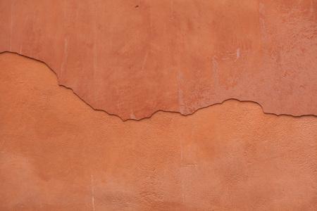 Vieux mur de stuc peint en terre cuite avec du plâtre fissuré. Texture d'arrière-plan