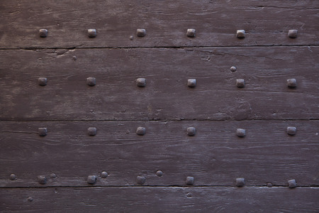 rivets: Brown painted wooden gate fixed with rivets. Background texture.