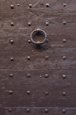 doorknocker: Old metal doorknocker on the brown painted wooden gate fixed with rivets in Bergamo, Lombardy, Italy.