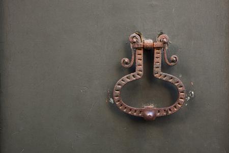 doorknocker: Old rusty doorknocker on the metal gate in Bergamo, Lombardy, Italy.