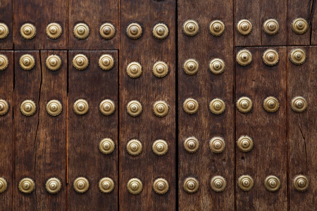 rivets: Old wooden gate fixed with large brass rivets in Cordoba, Andalusia, Spain. Stock Photo