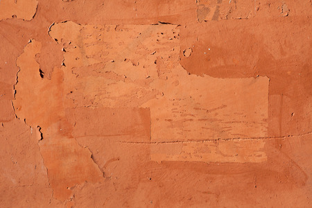 stucco wall: Traces of old announcements seen on terracotta painted stucco wall. Background texture.