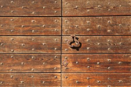 doorknocker: Old metal doorknocker on the wooden gate fixed with rivets in Bergamo, Lombardy, Italy.