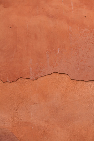 stucco wall: Old terracotta painted stucco wall with cracked plaster. Background texture. Stock Photo