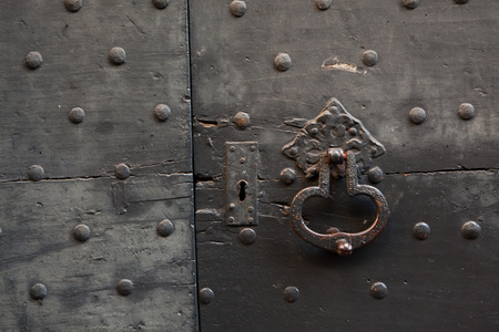 doorknocker: Old metal doorknocker on the black painted wooden gate fixed with rivets in Bergamo, Lombardy, Italy.