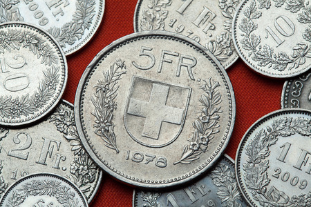 swiss insignia: Coins of Switzerland. Coat of arms of Switzerland depicted in the Swiss five franc coin.