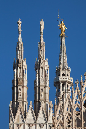 virgen maria: Gilded bronze statue of the Virgin Mary called the Madonnina on the spire of the Milan Cathedral in Milan, Lombardy, Italy.