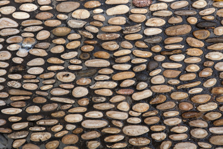 stone background: Cobbled pavement made of river rounded pebbles in Cordoba, Andalusia, Spain. Background texture.
