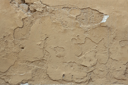 stucco wall: Old ochre painted stucco wall with cracked plaster. Background texture.