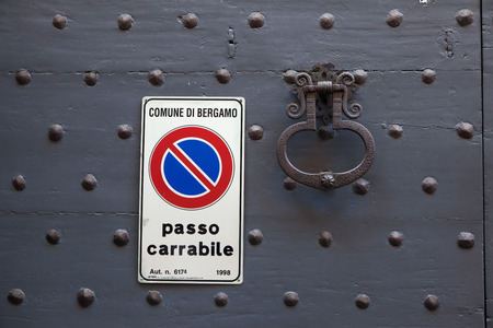 doorknocker: BERGAMO, ITALY - NOVEMBER 4, 2015: Old metal doorknocker and the No Parking sign on the black painted wooden gate fixed with rivets in Bergamo, Lombardy, Italy.