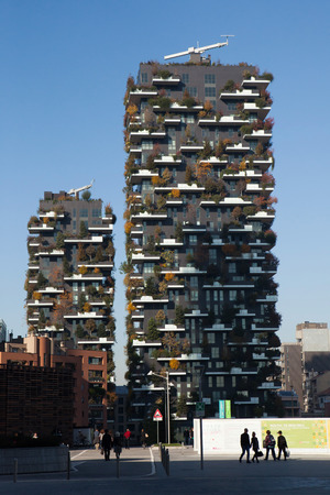 bosco: MILAN, ITALY - NOVEMBER 8, 2015: People pass by the Bosco Verticale (Vertical Forest) residential towers in the Porta Nuova district in Milan, Lombardy, Italy.