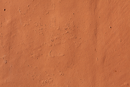 stucco wall: Terracotta painted stucco wall. Background texture.