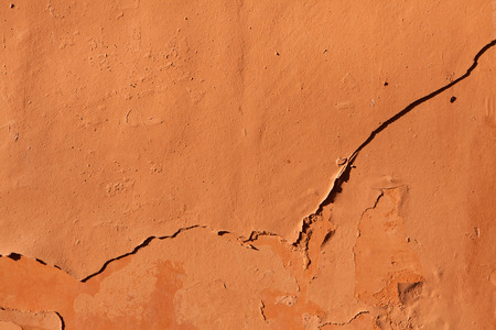 stucco wall: Old terracotta painted stucco wall with chipped paint. Background texture.