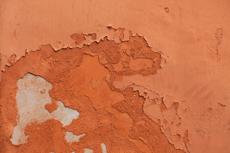 Old terracotta painted stucco wall with chipped paint. Background texture.