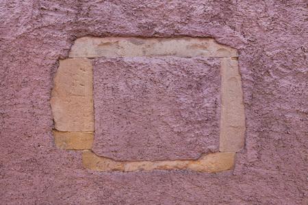 stucco: Burgundy red painted stucco wall.