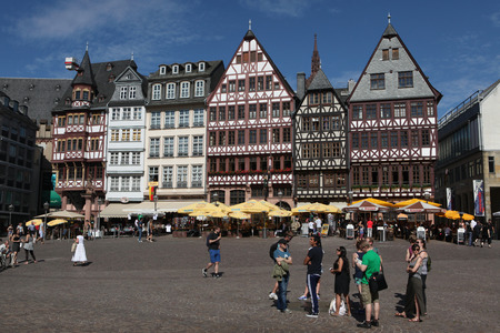reconstructed: FRANKFURT AM MAIN, GERMANY - JUNE 14, 2015: Tourists in front of the reconstructed half-timbered houses of the Ostzeile at the Romerberg in Frankfurt am Main, Germany.