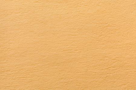 ochre: Yellow ochre painted stucco wall. Background texture.