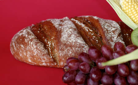 loaf of bread, with grapes and corn on red background