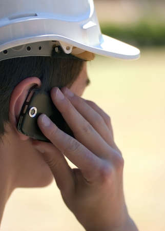 Man in hard hat on mobile phone Stock Photo