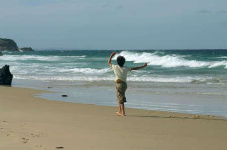 Boy on surf beach conducting the sea