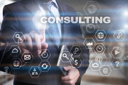 """Biznesmen naciska na wirtualny ekran i wybiera """"Konsulting""""."""