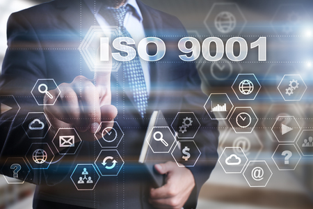 Businessman is pressing on the virtual screen and selecting ISO 9001. Stock Photo
