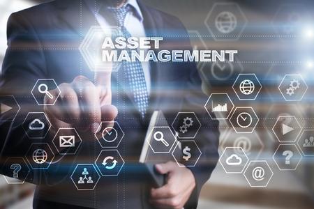 """L'homme d'affaires appuie sur l'écran virtuel et sélectionne """"Asset management""""."""
